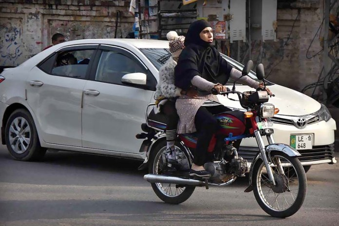 A women riding motorcycle without wearing safety helmet