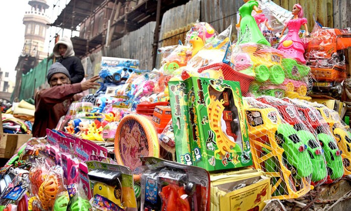 A vendor arranging and displaying different kinds of Plastic Toys on their handcart at walled city in the Provincial Capital