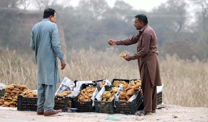 A vendor showing Gur to a customer at his roadside setup in the outskirts of the city