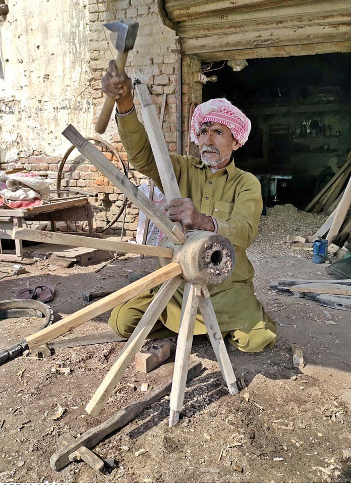 A worker busy in repairing donkey cart wheel at his workplace