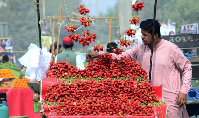A vendor arranging and displaying strawberries to attract the customer on his handcart