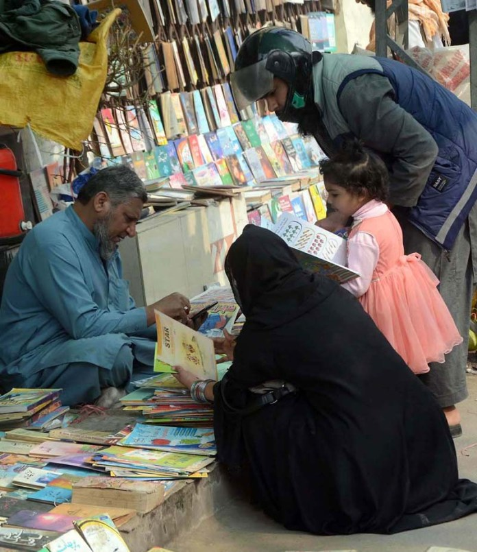 A couple selecting and purchasing old books for child at roadside stall