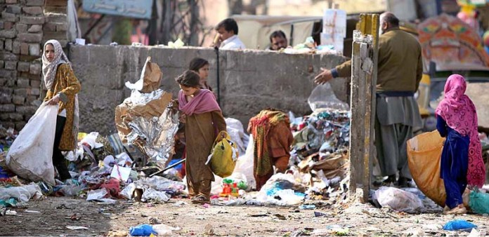 Gypsy children searching valuables from pile of garbage at a residential area of Tipu Road