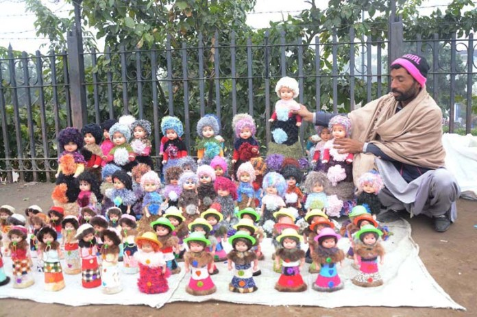 Vendor arranging and displaying colorful dolls to attract the customers at his roadside setup