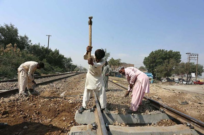 Railway workers busy in maintenance work on railway track at near autobahn road