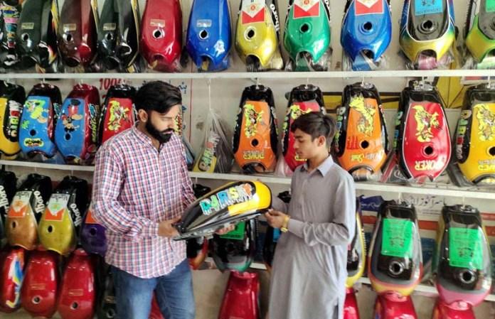 A person selecting colorful petrol tank for his motorcycle at Bakrani Road