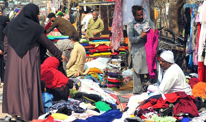 Ladies selecting and purchasing second hand clothes displayed by a roadside vendor