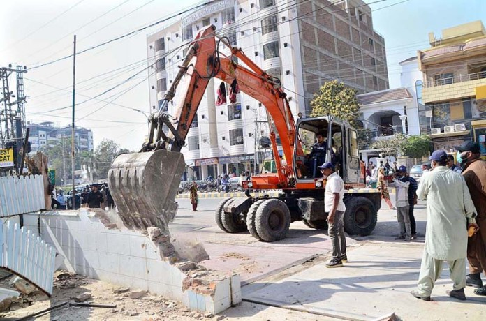 Staffers of Anti Encroachment Cell demolishing encroachments at Latifabad