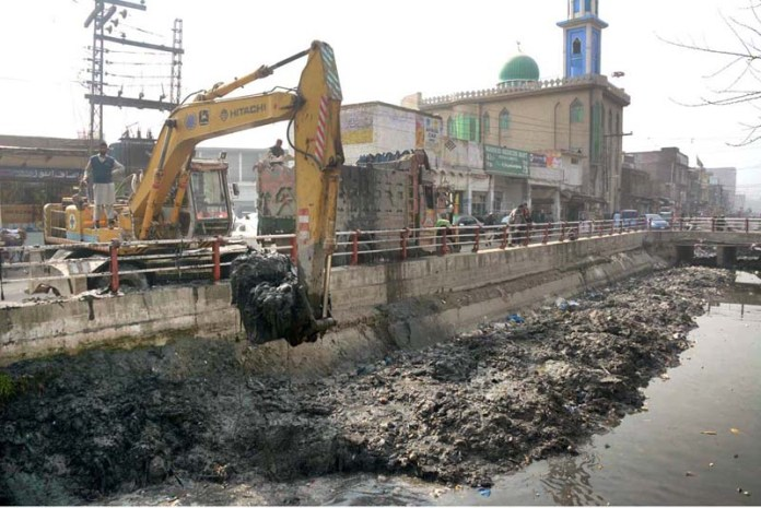 Labourers cleaning Qadirabad Canal with the help of heavy machinery