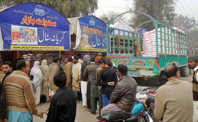 People standing in queue for buying flour bags from Sahulat Bazaar at Sargodha Road