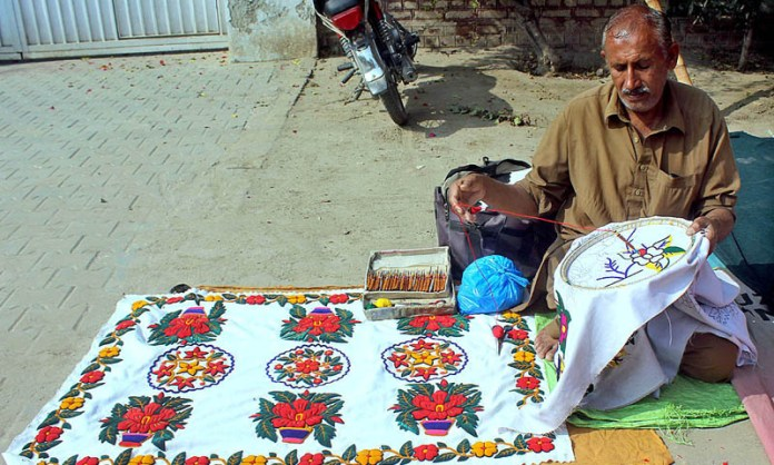 Worker busy in embroidery work on the cloth at his roadside setup