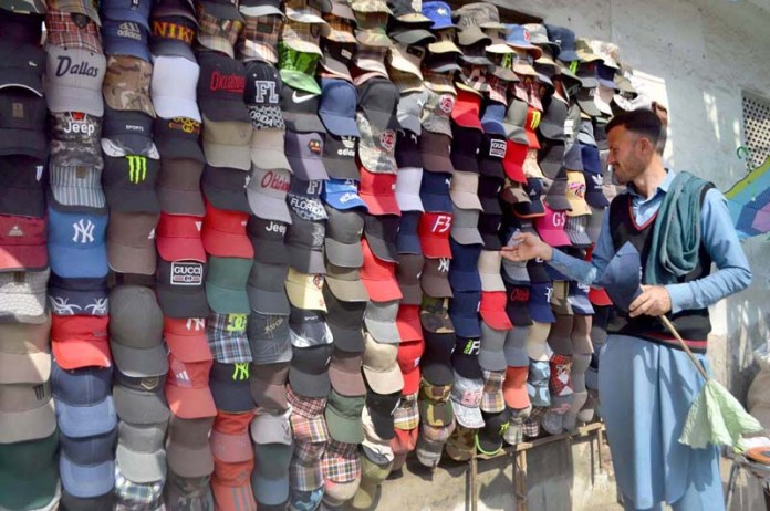 Vendor busy in arranging and displaying caps to attract the customer at his roadside setup