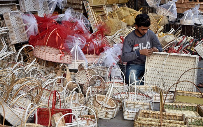 Worker preparing colourful traditional baskets with tree branches at his workplace