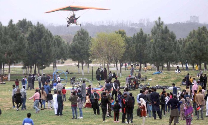 Visitors enjoying paragliding during Islamabad Tourism Festival containing aerial shows, paragliding, adventure sports, vintage cars & bike, horse parades, concerts, food court etc at Fatima Jinnah Park