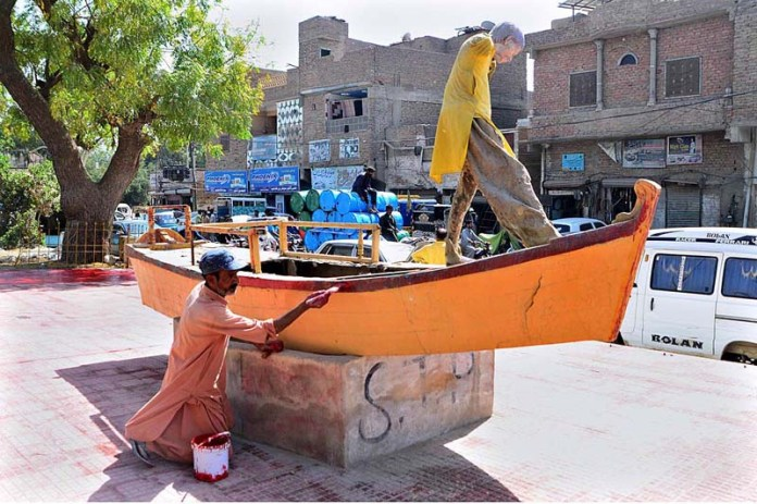 A painter paints on the replica of a boat displayed at a roadside at Kotri Road