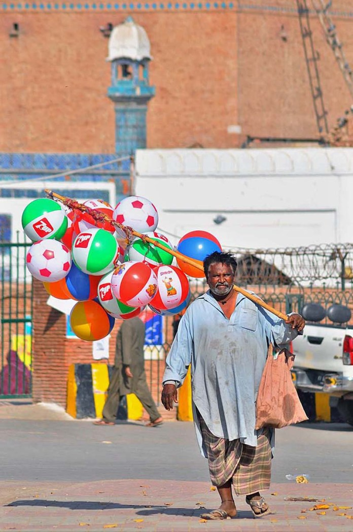 A street vendor displaying air filled plastic balls to attract the customers at Qasim Bagh Road