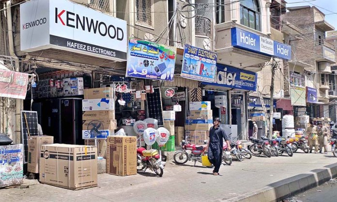 A view of open shops in violation of the SOPs for COVID-19 pandemic at Pakistan Chowk Road during lockdown as Sindh government has announced to keep the market closed on Friday and Sunday during precautionary measures of COVID-19 pandemic