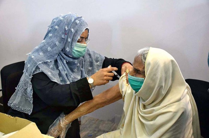 A health worker administering the corona vaccine to an elderly woman at Sports Complex
