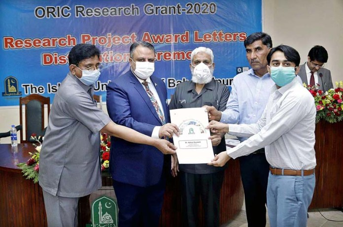 Prof. Dr. Athar Mahboob, Vice Chancellor giving research award to scholar during a ceremony at University of Bahawalpur