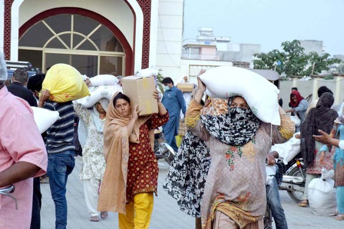 Women carrying Ramadan rations on their heads and back to home from ration distribution point