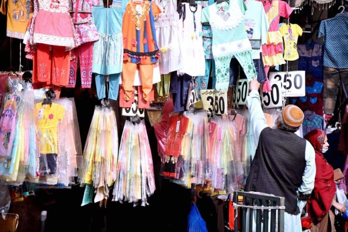 A couple busy in shopping from a stall ahead of the Eid al-Fitr at Kashmir Bazar