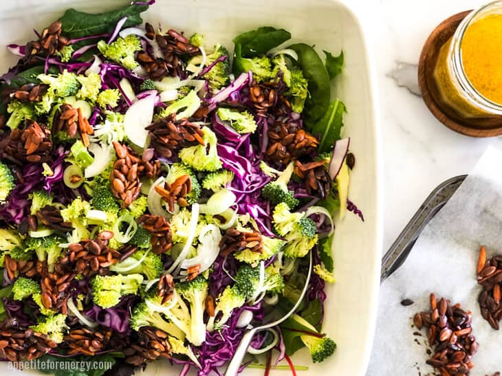 Crunchy Broccoli Slaw in a white serving bowl with nut clusters and dressing in a jar