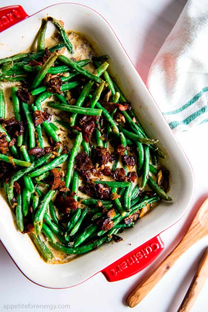 Keto Sautéed Green Beans with Bacon Cream Sauce in a white serving dish on the dining table with napkin, wooden spoon