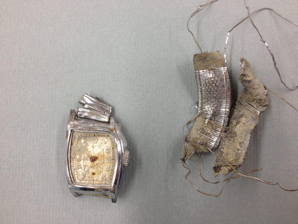 Pilotens ur blev fundet sammen med andre personlige genstande, som nu udstilles i en begrænset periode. Uret er ødelagt, og viserne mangler. Det er tilsyneladende gået i stå på nedstyrtningstidspunktet. Ud fra resterne af viserne var tidspunktet formentlig omkring kl. 14. Museet er ikke i tvivl om, at det er pilotens ur, fordi hans initialer er indridset på bagsiden, HW – Hans Wunderlich. (Foto: © Nordjyllands Historiske Museum)