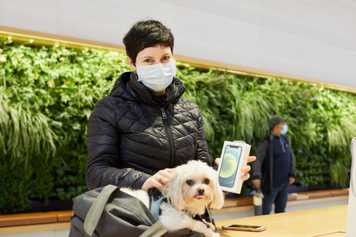 Una cliente con un cagnolino tiene in mano il suo nuovo iPhone 12 mini.
