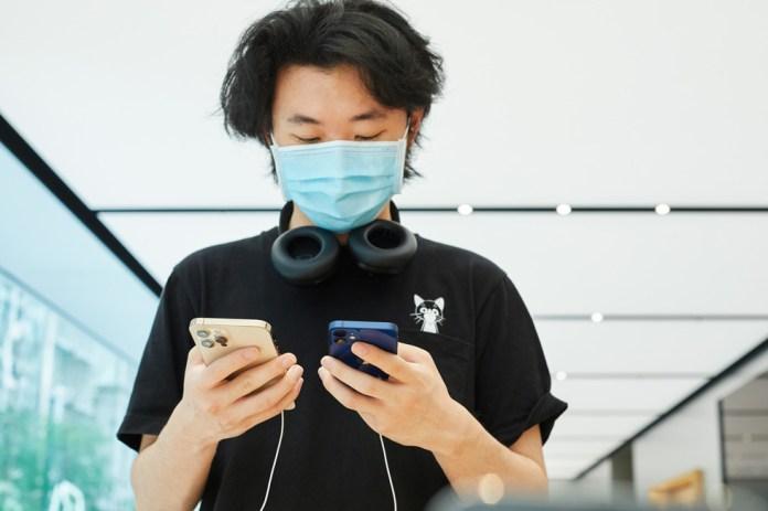 Un cliente di Apple Sydney confronta iPhone 12 Pro Max e iPhone 12 mini.