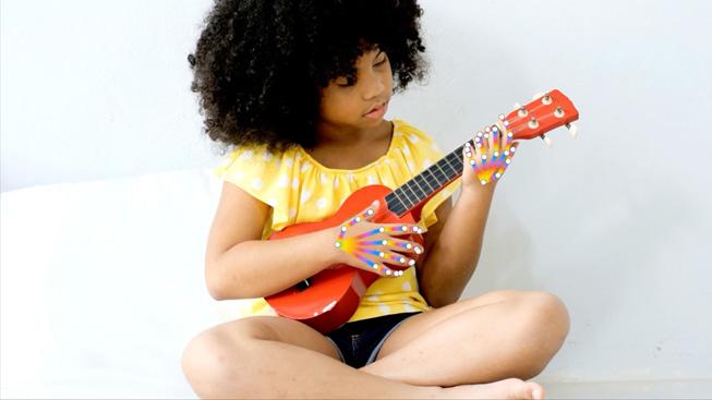 Un bambina suona un ukulele per dimostrare il rilevamento della posizione delle mani.