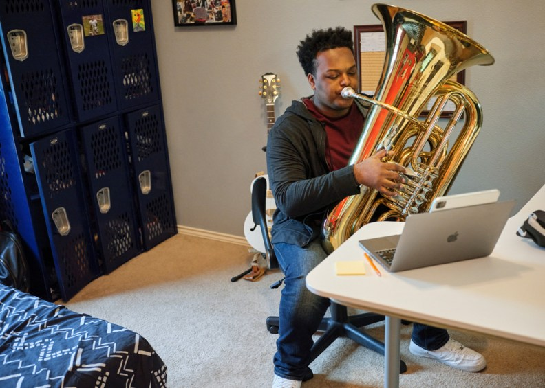 Rhys Richard practices the tuba alongside iPad Pro and MacBook Pro.