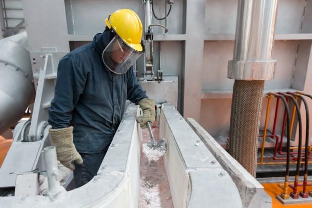 Trabalhador monitora processo de fusão em fábrica de alumínio.