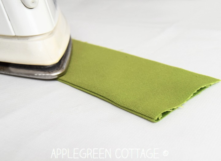 folded green fabric to finish a French seam