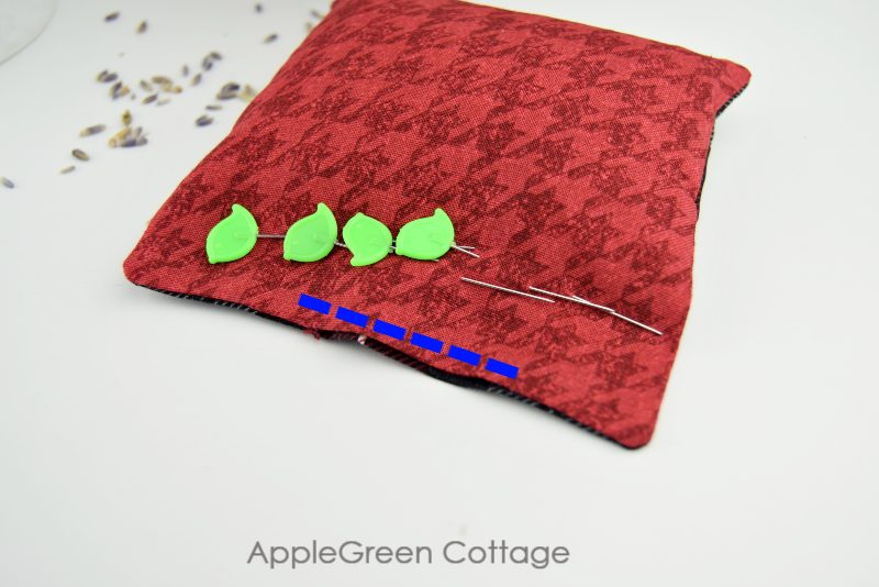 green pins on a semi finished square hand warmer