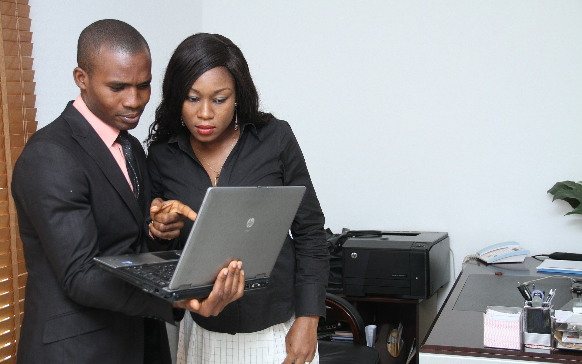 Man and woman looking at laptop in office
