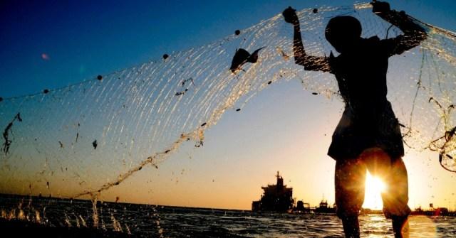 22abr2013---pescador-procura-por-peixes-em-rede-com-navio-petroleiro-ao-fundo-no-porto-de-duba-na-arabia-saudita-1366666094520_956x500