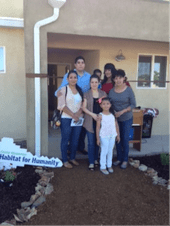 Maria and her family in front of her new Habitat for Humanity Home