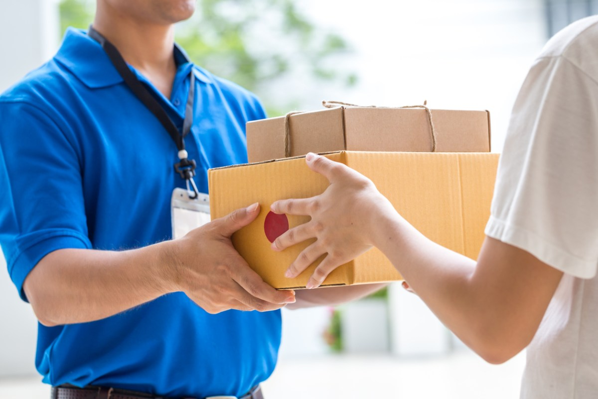 A delivery man in a blue shirt delivering a package to a customer.