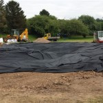 Pull and adjust the pond liner to remove wrinkles