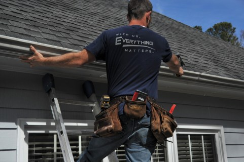 Crew working on roof with WIth us, everything matters shirt
