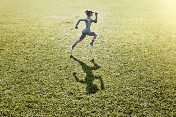 Vrouw doet aan run-walk-exercise hardlooptraining op een sportveld