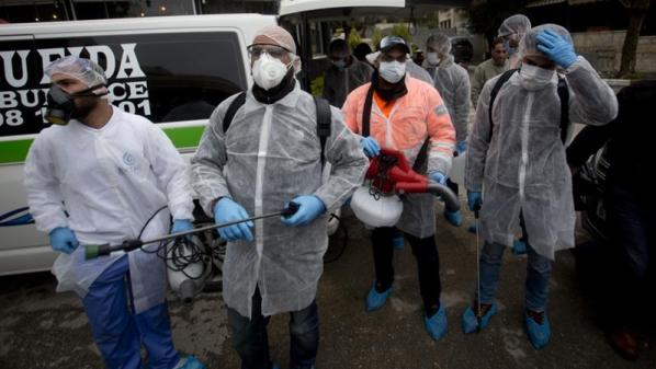 Image: Palestinian workers get ready to disinfect mosques and churches in the West Bank city of Ramallah. Photo: Majdi Mohammed/AP