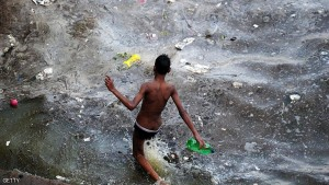 An Indian youth walks into polluted flood waters after the river Ganges rose following heavy monsoon rains in Allahabad on July 10, 2016. / AFP / SANJAY KANOJIA        (Photo credit should read SANJAY KANOJIA/AFP/Getty Images)