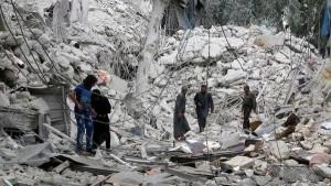 سكان وسط انقاض منزل دمرته طائرات حربية في حلب بسوريا يوم الجمعة. تصوير: عبدالرحمن اسماعيل - رويترز