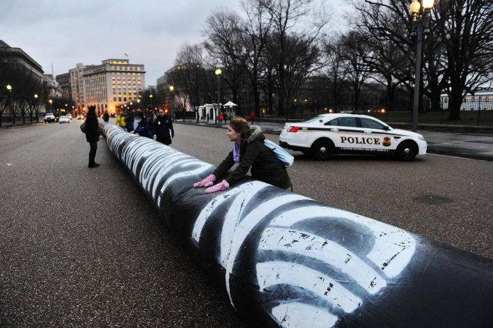 In this file photo taken on Feb. 03, 2014, environmental activists inflate a long balloon to mock the Keystone pipeline project during a rally in front of the White House in Washington, DC. (AFP / JEWEL SAMAD)