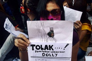 Seorang perempuan aktivis Front Pekerja Lokalisasi (FPL) menunjukkan surat yang akan dikirimkan ke Komnas HAM saat aksi penolakan rencana penutupan lokalisasi Dolly yang digelar di kawasan lokalisasi Dolly, Surabaya, Jawa Timur, Kamis (5/6).