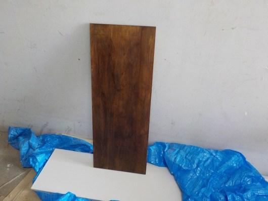 トイレの棚板がポリ化粧板で味気なかったので、自然の風合いを取り入れたく思い、木材をカットして塗装しました。下に敷いてあるライトグレーの板が元の棚板です。