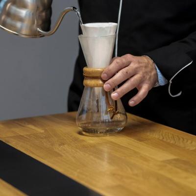 Préparation du café sur le Table connectée en chêne et pierre acrylique noire.