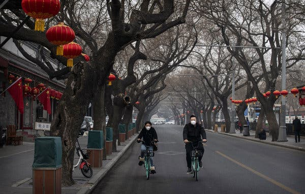 In Beijing on Sunday, riders wearing protective masks cycle on a nearly empty street that is normally busy with tourists.Credit...Kevin Frayer/Getty Images